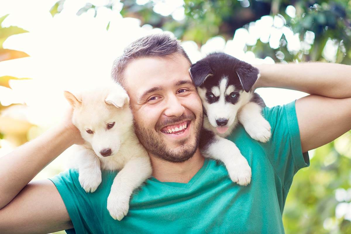man with two puppies
